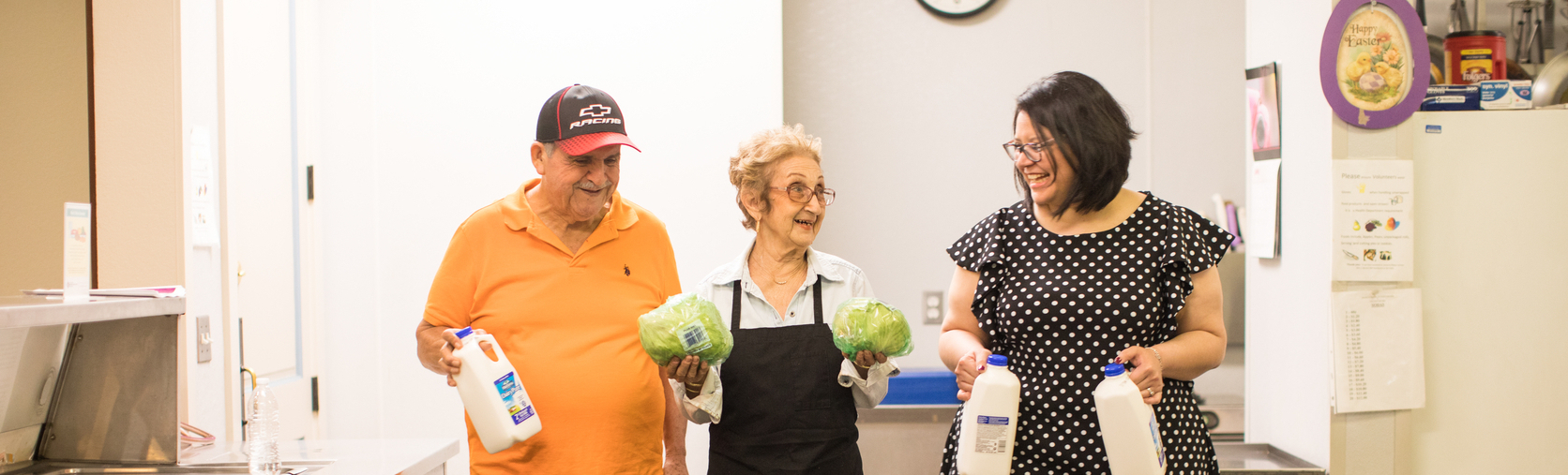 Residents Cruz Arrieda (orange shirt) and Victoria Marotta (older woman in apron) also volunteer in the kitchen. Crystal Reuwjo (Community Engagement Manager at MAUC ) also helping - seen on the right.